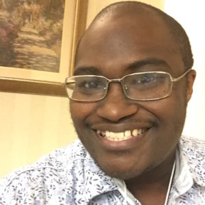 A picture of a smiling 30ish black man in glasses.