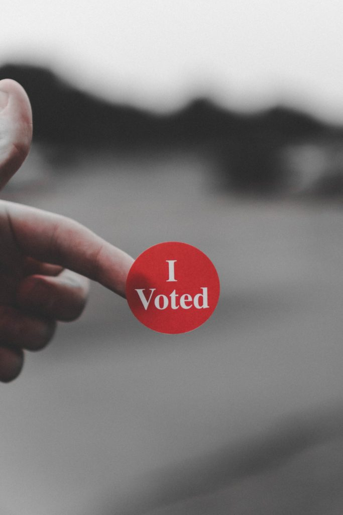 A close-up photo of a finger with an 'I voted' sticker on it. Photo by Parker Johnson on Unsplash.