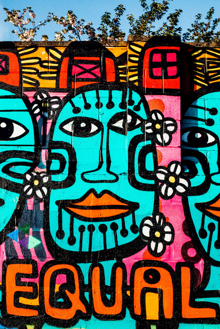 A colourful mural depicting stylised people, with the text EQUAL.