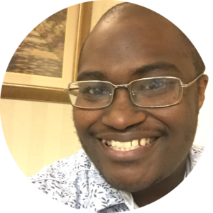 a picture of a smiling black man with shaved black hair, glasses and a blue and white flowered shirt.